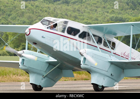 A De Havilland DH89A Dragon Rapide from Scillonia Airways, registration G-AHAG, with the pilot, photographed on the ground at Wellesbourne airfield. - Stock Photo