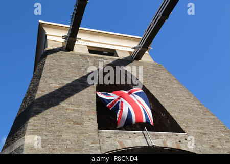 Union Jack flag flying in the arch of one of the support pylons of the Clifton Suspension Bridge in Bristol UK - Stock Photo