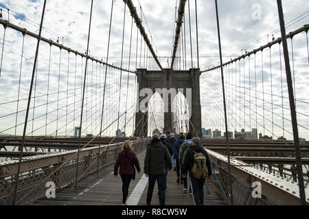 Tourists walk on the famous Brooklyn Bridge in Manhattan, New York, United States. - Stock Photo
