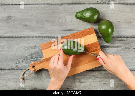 Tabletop view, woman hands holding chef knife, cutting avocado on chopping board, two whole avocados near on gray wood desk. - Stock Photo