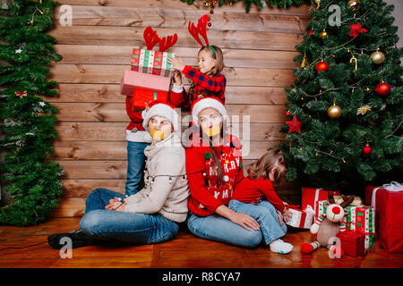 Bad kids and father and mother tied up with garland near Christmas tree at home - Stock Photo