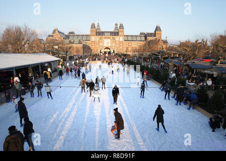 People skating and enjoying on the ice rink at outside the Rijksmuseum (Background) in Museum Square on December 14, 2108 in Amsterdam, Netherlands. A - Stock Photo