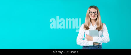 Portrait young caucasian woman worker teacher trainer mentoring in white shirt office style long hair with a tablet in hand uses technology isolated b - Stock Photo