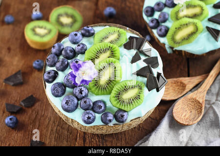 Blue spirulina and berry smoothie bowl, fresh blueberries, kiwi and chocolate pieces with wooden spoons served in coconut bowls over a rustic backgrou - Stock Photo