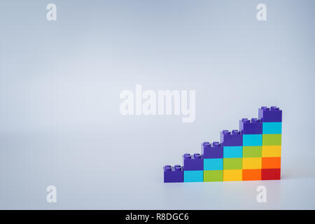 Colorful rainbow colored ascending stacks made of toy building bricks on gray background. Copy space. - Stock Photo
