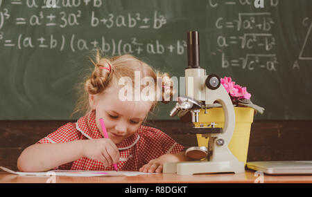 Little girl study in chemistry classroom at school. Schoolgirl work on chemistry research with microscope, vintage filter - Stock Photo