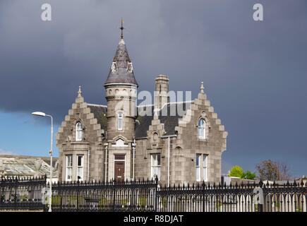 Victorian Scots Baronial Gatehouse. Trinity Cemetery, Aberdeen, Scotland, UK. Ornate Granite House against a Foreboding Grey Sky. - Stock Photo