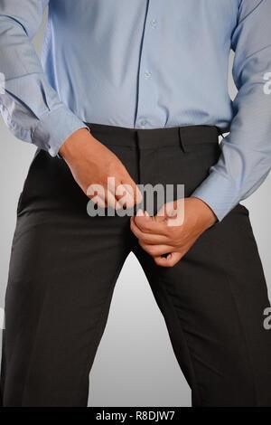 Photo image of a businessman dressing, pulling his pants zipper. Closeup shot of male waist dressing, wearing a pants. Formal wear - Stock Photo