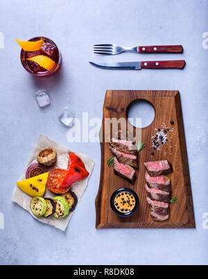 Medium Beef Rib Eye steak slices on wooden board with grilled vegetables and drink. Top view - Stock Photo