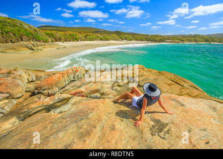 Woman in hat sunbathing on the rocks of Waterfall beach in Denmark, Western Australia. Caucasian tourist looking Great Southern Ocean in William Bay NP. Summer destination in Australia. - Stock Photo
