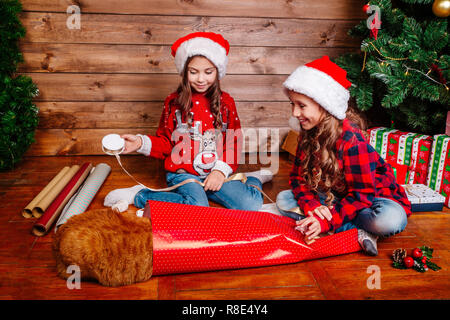 Happy funny little sisters in Santa hats pack gifts near Christmas tree - Stock Photo