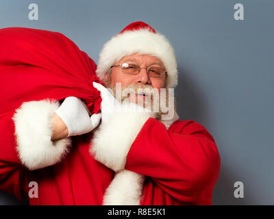 Santa Claus is holding a huge bag of gifts on his shoulder. Christmas miracle, celebration and gifts concept. - Stock Photo
