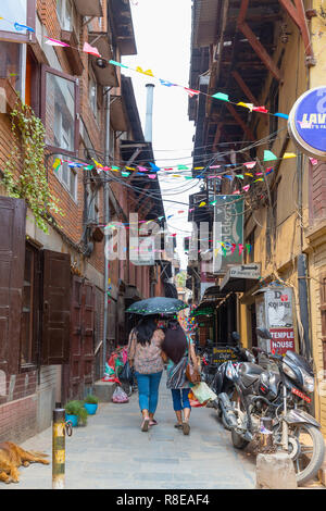 Mother and daughter holding an umbrella and walking down street in  Patan, Lalitpur,  Nepal. - Stock Photo