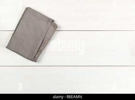 Grey dishcloth on white wooden plank table flat lay top view from above with copy space - Stock Photo