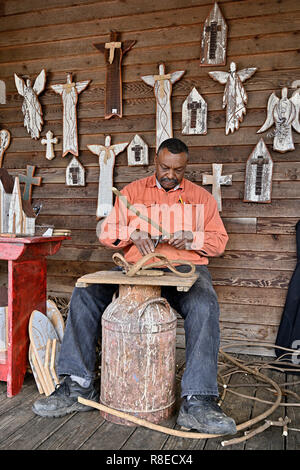 Black or African American woodworking artist making wooden figures and figurines for sale on the porch of Priester's Pecans near Fort Deposit Alabama. - Stock Photo