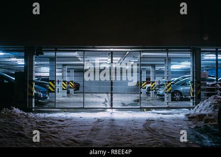 Apartment based illuminated parking with cars inside on winter night backdrop - Stock Photo