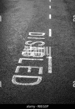 Disabled parking bay markings on a tarmac road - Stock Photo