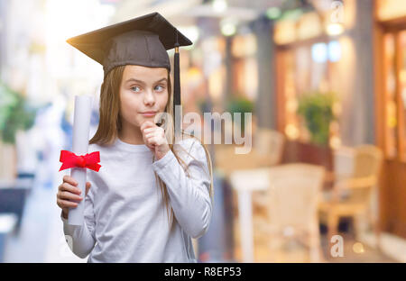 Young beautiful girl wearing graduate cap holding degree over isolated background serious face thinking about question, very confused idea - Stock Photo