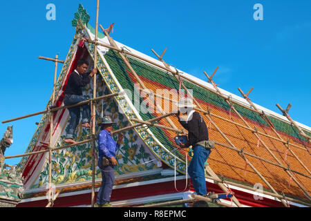 Workers repairing the roof of a clerical building in the grounds of Wat Po, Bangkok, Thailand - Stock Photo