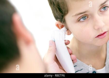 Boy having his temperature taken with a digital thermometer. - Stock Photo