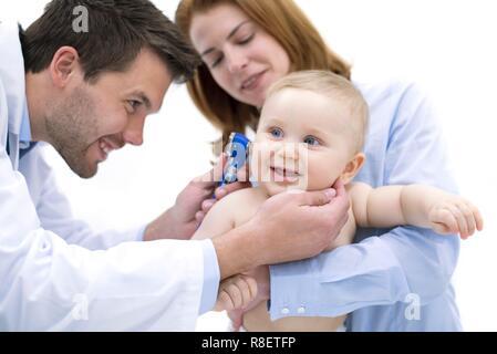 Doctor examining baby boy's ear with otoscope. - Stock Photo