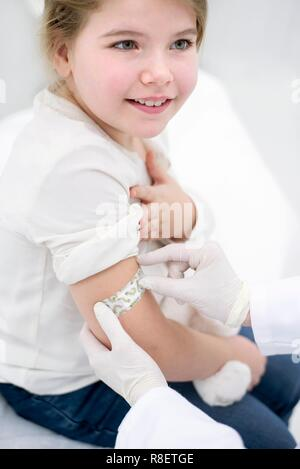 Doctor sticking plaster on young girl's arm after injection - Stock Photo
