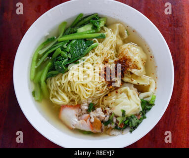 soup noodle wonton roasted pork / yellow egg noodle with red roast pork dumpling and chinese cabbage vegetable in soup bowl on wooden table top view - Stock Photo