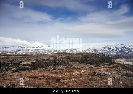 Tectonic plates collide in the Mid-Atlantic rift valley of Thingvellir National Park, Iceland. Volcanic landscape, with colourful rock fissures - Stock Photo