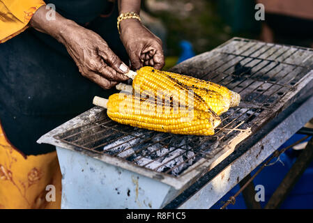 Old rural asian woman cook corn cobs on the grill. Close up image with corn and hands. Classic asian street food from Langkawi island in Malaysia. - Stock Photo