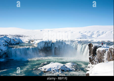 Godafoss, northern Iceland. Spectacular scene, frozen waterfall in winter, Person stands on rocky ledge viewing semicircular falls - Stock Photo