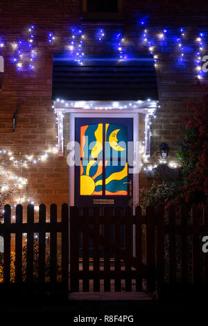 Sun and moon stained glass door and christmas lights on a house in Bloxham. Bloxham, Oxfordshire, England - Stock Photo