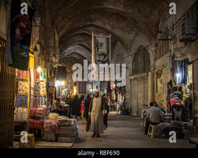 ISFAHAN, IRAN - AUGUST 20, 2018: Islam passing under a towel shaped like a US Dollar bill in the Isfahan bazar in the evening. The iranian rial, iran  - Stock Photo