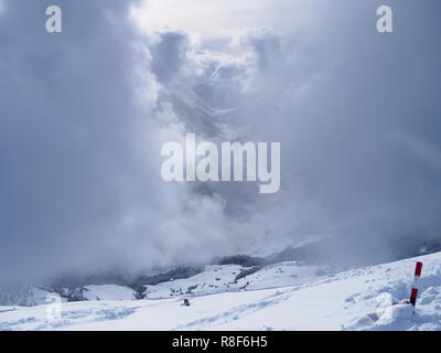 Dense dark clouds nearly shadowing high alpine scenery in Austria - Stock Photo