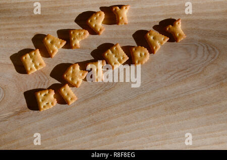 Happy birthday. Text from the salty crackers as printed English letters that lie on a wooden chopping board. Message, lined with edible letters