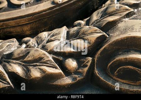 Laurel wreath  close-up dark bronze metal cast background. Vintage leaves and berries sculpture art detail - Stock Photo