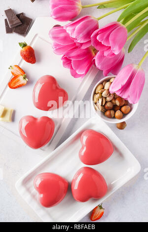 Red heart shaped mousse cakes with berries and chocolate. - Stock Photo