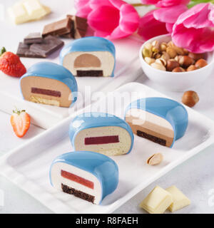 Set of blue heart shaped mousse cakes with various fillings. - Stock Photo