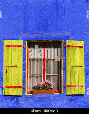 Beautiful old window with red flowers on the old rusty house. Blue facade. City of Nyon, canton Vaud Switzerland - Stock Photo