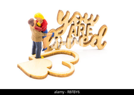 Miniature figures as in love hugging couple next to You Are Loved wooden sign, isolated on white background - Stock Photo