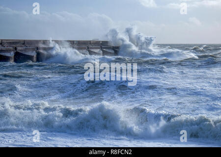 Dramatic stormy sea breaking against Brighton marina black stone harbour wall, spray and waves high in the air, rough sea, Brighton, East sussex, Uk - Stock Photo