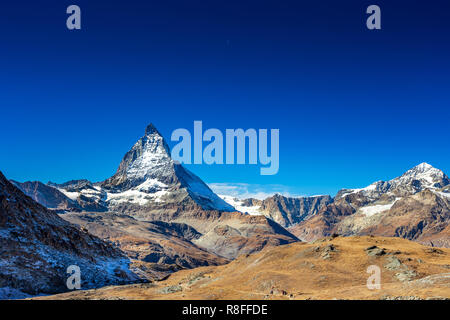 Matterhorn peak mountain for trekking hiking from tourist in summer with clear blue sky and day moon at Zermatt Switzerland, Europe - Stock Photo