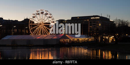 Christmas Market by Lille Lungegaardsvannet Lake in downtown Bergen, Norway. Ferris wheel and tents. - Stock Photo