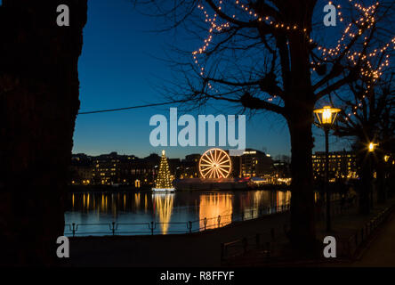 Christmas tree and Market by Lille Lungegaardsvannet Lake in downtown Bergen, Norway. Ferris wheel rotating. - Stock Photo