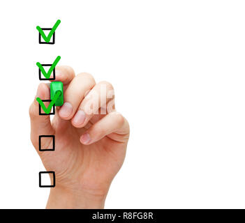 Hand putting three check marks with green marker on blank customer survey checklist on transparent glass board. - Stock Photo