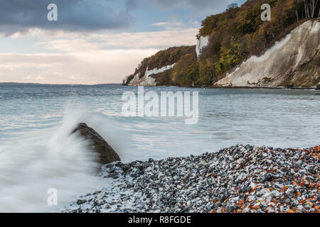 Chalk cliffs in the morning with dramatic clouds in the National Park Jasmund on the island of Rügen. Wave hits over a stone. White water on the beach