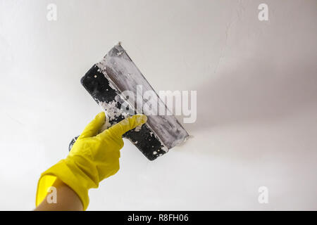 worker's hand in yellow gloves holding putty knife patching a hole with spatula with plaster or putty in white wall. Renovation and repair process, re - Stock Photo