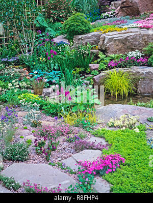 Colourful alpine Rockery and waterfall for a country garden - Stock Photo
