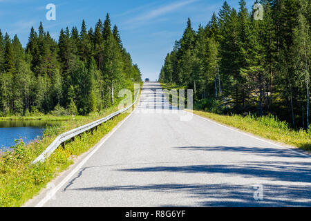 Countryroad though a typical landscape in Finland with trees and water - Stock Photo