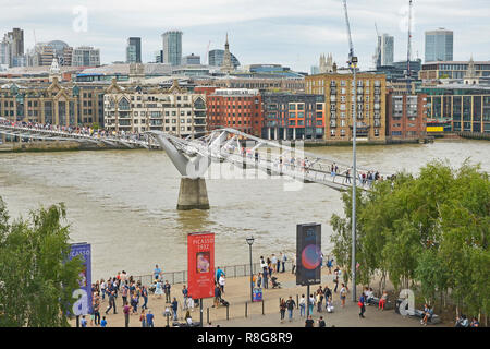THE MILLENNIUM BRIDGE, THAMES EMBANKMENT, LONDON. AUGUST 2018. The Millennium Footbridge asuspension bridge over the River Thames with the skyline of  - Stock Photo