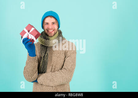 Winter fashion knitted clothes. Knitted accessories as hat and scarf. Man knitted hat gloves and scarf winter fashion. Man wear knitted accessory turquoise background. Winter accessories concept. - Stock Photo